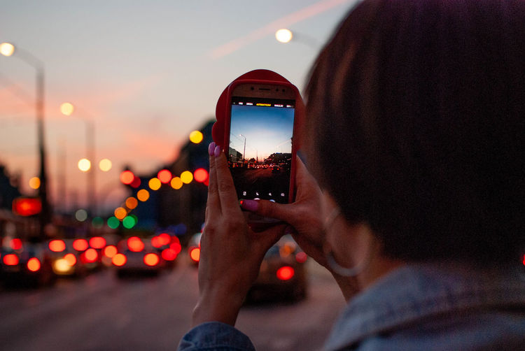 Midsection of man photographing illuminated mobile phone in city