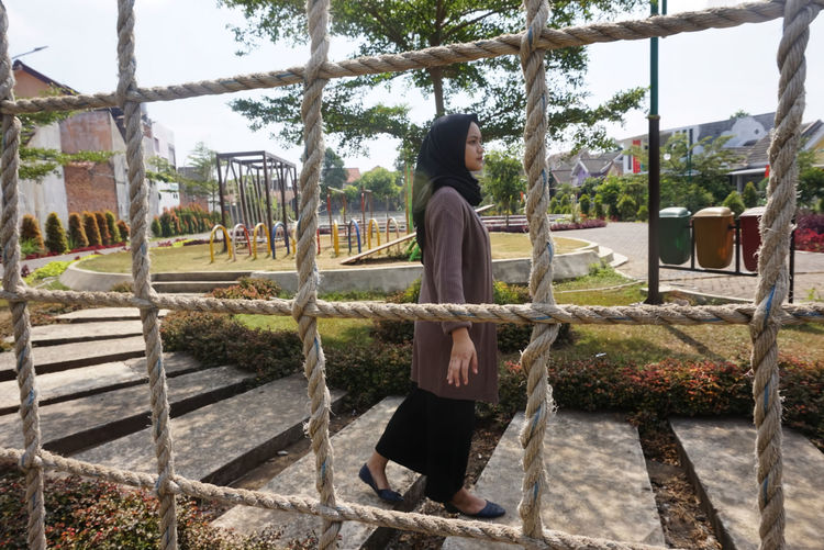 Rear view of woman sitting at park against sky