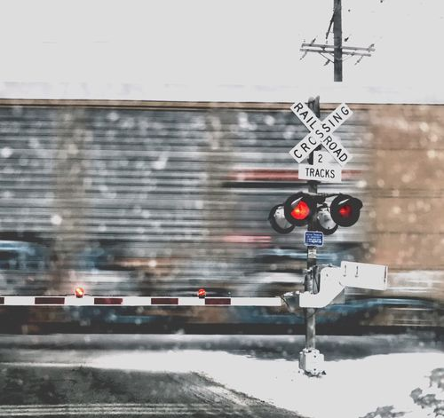 Guidance Transportation Road Sign No People Communication Day Outdoors Illuminated Crossing Sign Railroad Track Railroad Crossing Railroad Crossing Sign stopped by a train at a railroad crossing Train Moving Train Graffiti Train Train In Motion Crossing The Tracks Railroad Lights Winter Feeling Copy Space Roadblock Road Block Obstacles Grey Red Lights