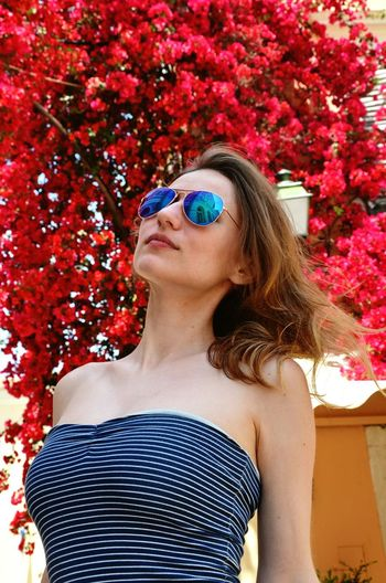 Beautiful young woman wearing sunglasses standing against red flowering plant