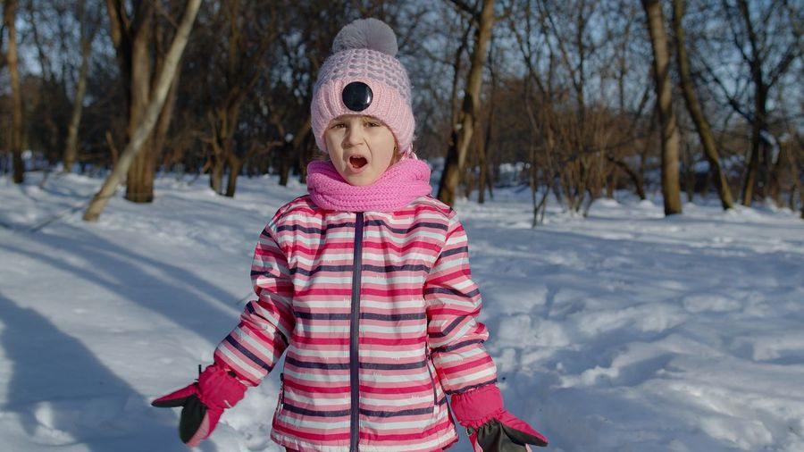 Full length of girl standing on snow covered field