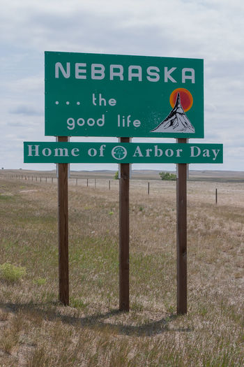 Close-up of road sign on field against sky
