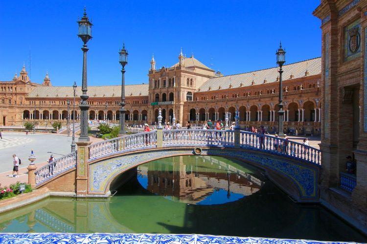 People walking in arch bridge at plaza de espana