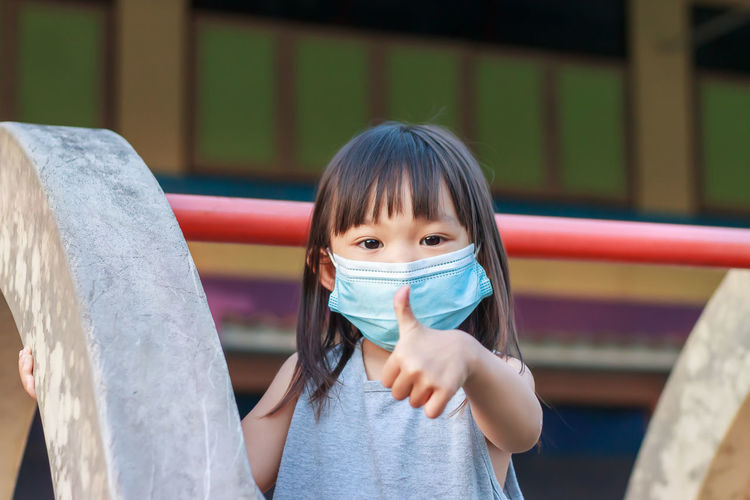 Portrait of girl wearing mask gesturing at playground
