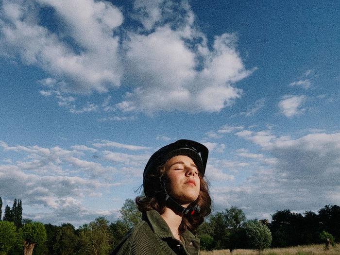 Portrait of teenage girl looking away against sky