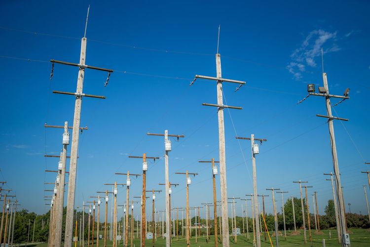 Telephone Pole Alternative Energy Blue Clear Sky Day Environment Environmental Conservation Fuel And Power Generation In A Row Low Angle View Nature No People Outdoors Pole Renewable Energy Rural Scene Sky Technology Turbine Wind Power Wind Turbine