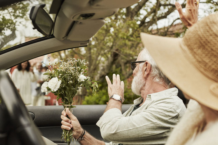Midsection of man holding umbrella while sitting in car