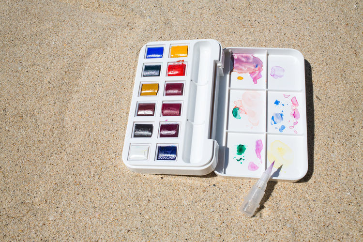 Watercolor box on beach background Artist Box Colors Creativity Objects PaintBox Rainbow Colors Textured  Travel Backgrounds Beach Brush Close-up Colorful Decoration Drawing Hobby Multicolors  Paintbrush Painting Plastic Sand Thailandtravel Watercolor Watercolor Painting