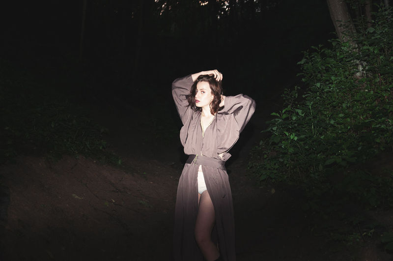 Portrait of young woman standing in forest at night