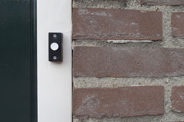 Black and white doorbell at the door of a living house Doorbell Bell Wall Wall - Building Feature Built Structure Brick Close-up Door Entrance Outdoors Push Button Brick Wall Architecture