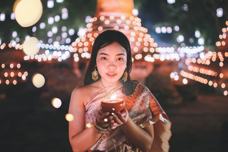 Let the light shine out of the darkness.✨🌖 Loy krathong festival young smiling woman holding a candle in your hand and bokeh background. Night Lights Nature Nightphotography Light Festival Women Light And Shadow Portrait Life Candle Happiness Night Lights Celebration Lighthouse Candlelight Standing Illuminated Beautiful Woman Loy Krathong Sukhothai Lifestyles Lighting Equipment Leisure Activity
