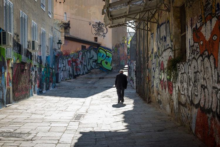 Full length of man walking on cobblestone