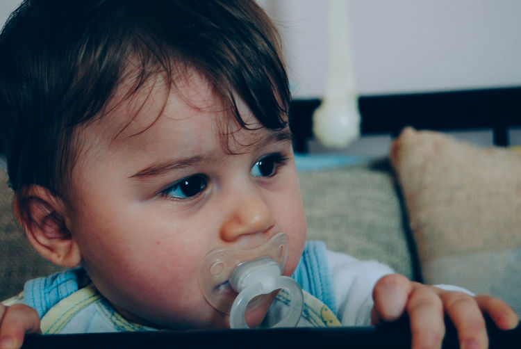 Close-up of baby boy with pacifier in mouth looking away at home