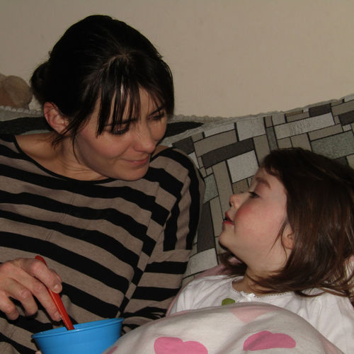Mother feeding daughter resting on sofa at home
