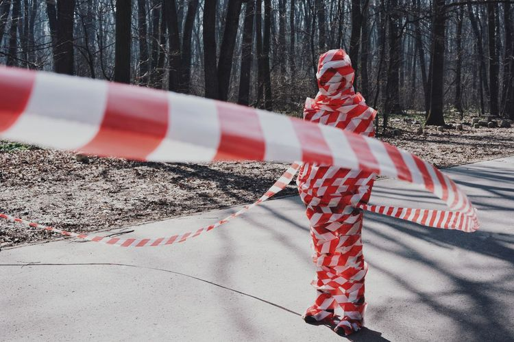 Person wrapped in signal tape on road