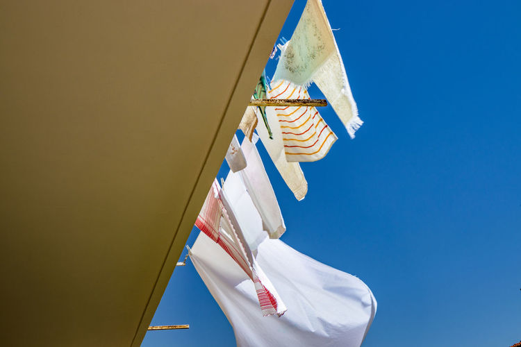 Low angle view of clothes hanging against clear blue sky