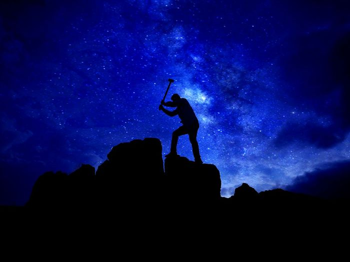 Silhouette man hammering rock against star field at night