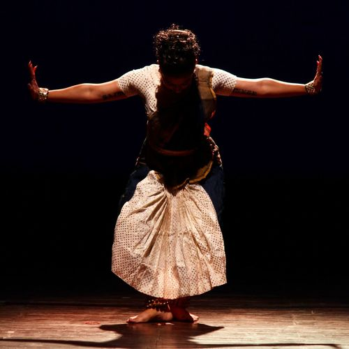 Full Length Of Mid Adult Woman Dancing On Stage Against Black Background