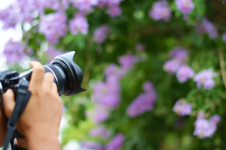 Midsection of person photographing camera