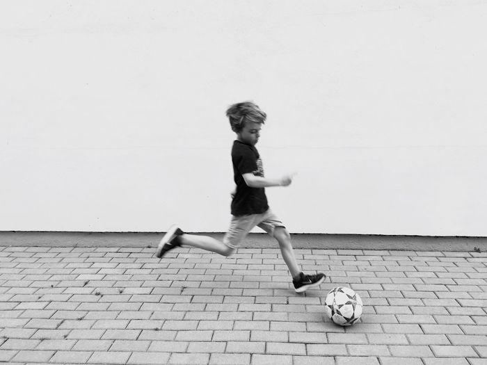 Full Length Of Boy Playing Soccer On Sidewalk Against Wall
