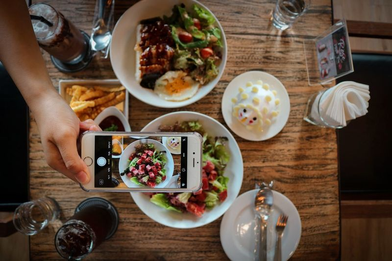 Food is lifestyle. Human Hand Wireless Technology Plate Eating Table Breakfast High Angle View Food And Drink Greek Salad