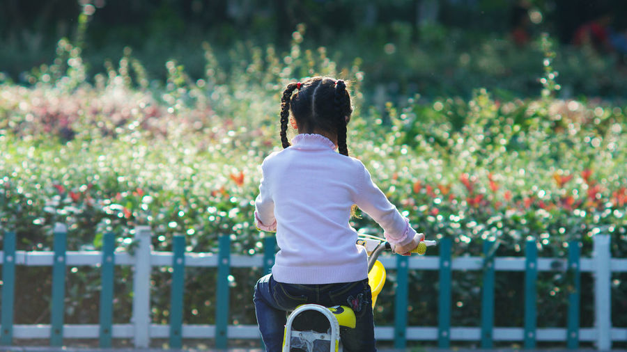 Rear view of girl cycling against plants
