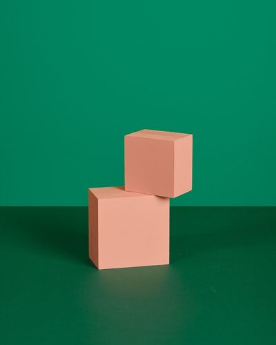 Close-up of coral colored cube shapes over green background