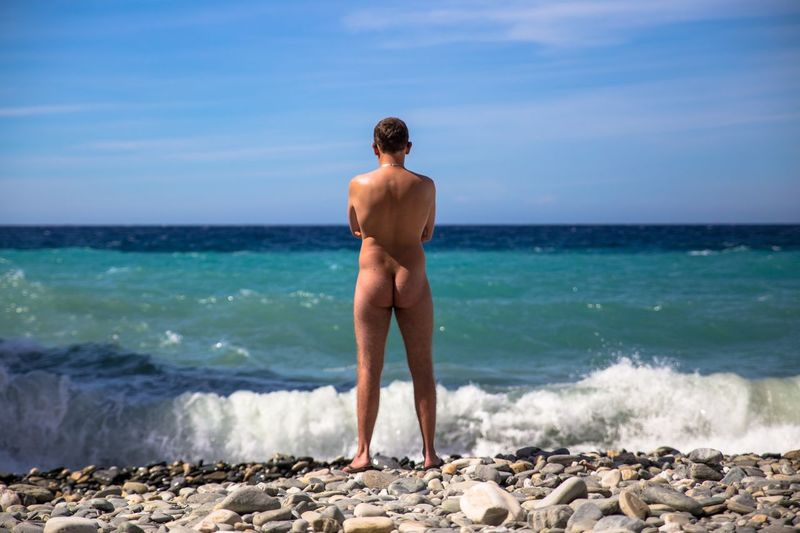 Rear view of naked man standing on pebble stones at beach