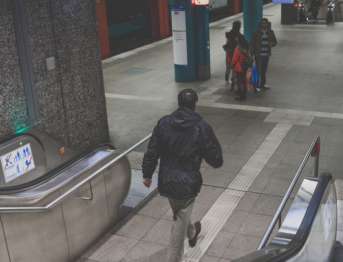 Rear view of people walking on railroad station