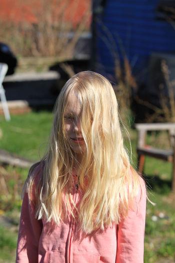 Smiling blond hair girl on field