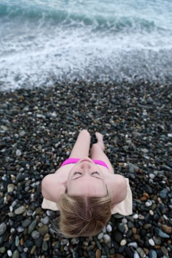 High angle view of teenage girl relaxing at pebbles covered beach
