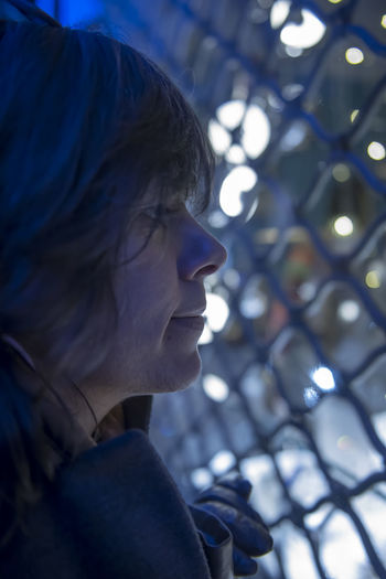 Profile view of thoughtful woman standing by fence at night