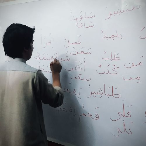 Rear view of man writing on whiteboard