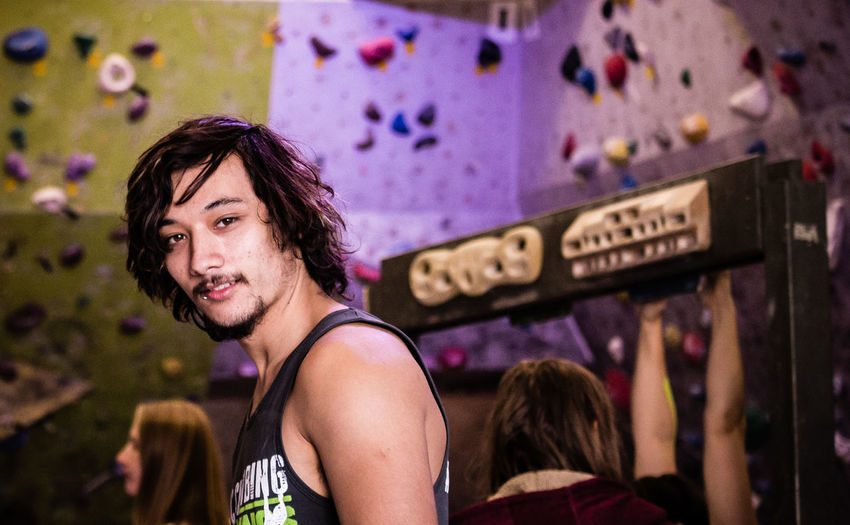 Portrait of young man against climbing wall