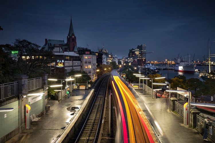 Light trails on illuminated railroad station at night