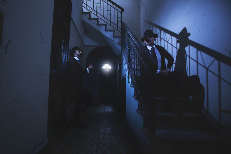 Men By Staircase In Darkroom