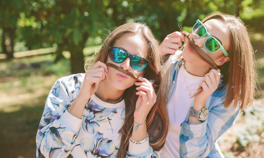 Two female friends with sunglasses having fun doing moustaches with their long hair. Relax and leisure time concept. Autumn Friends Fun Funny Green Horizontal Moustache Nature Woman Caucasian Emotion Female Forest Friendship Girl Hike Leisure Lifestyles Long Hair Mountain Outdoors Smile Summer Sunglasses Two People