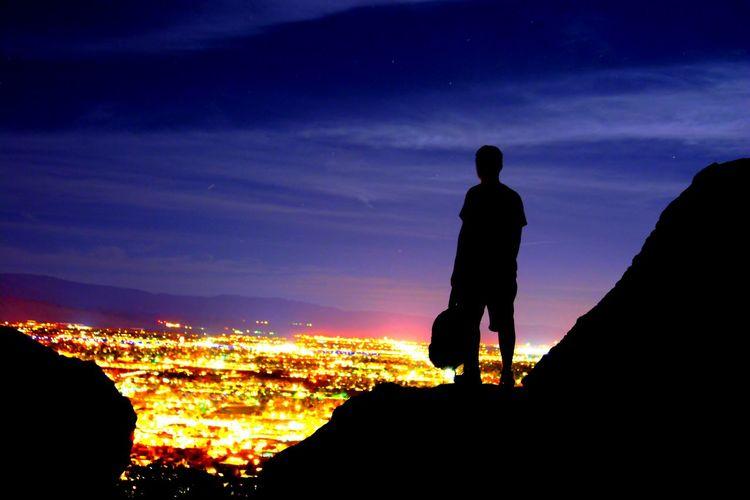 Silhouette man standing on mountain overlooking illuminated cityscape at night