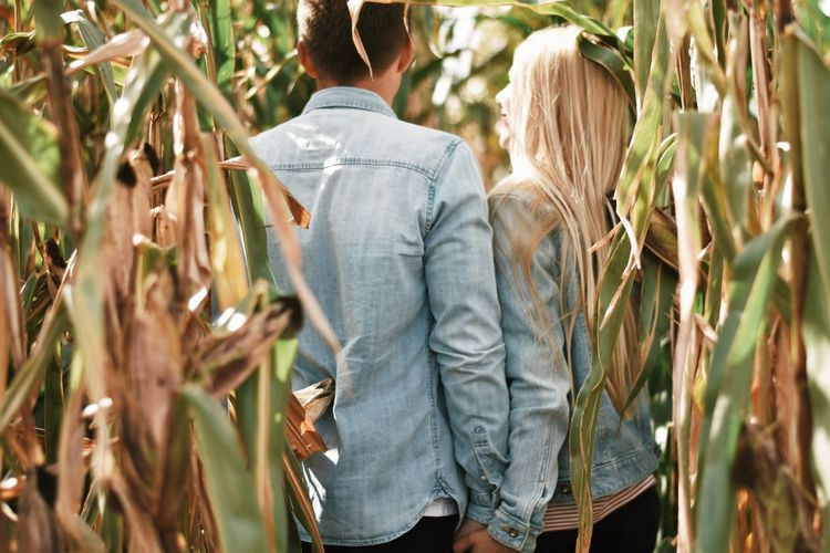 Rear view of couple standing by plants