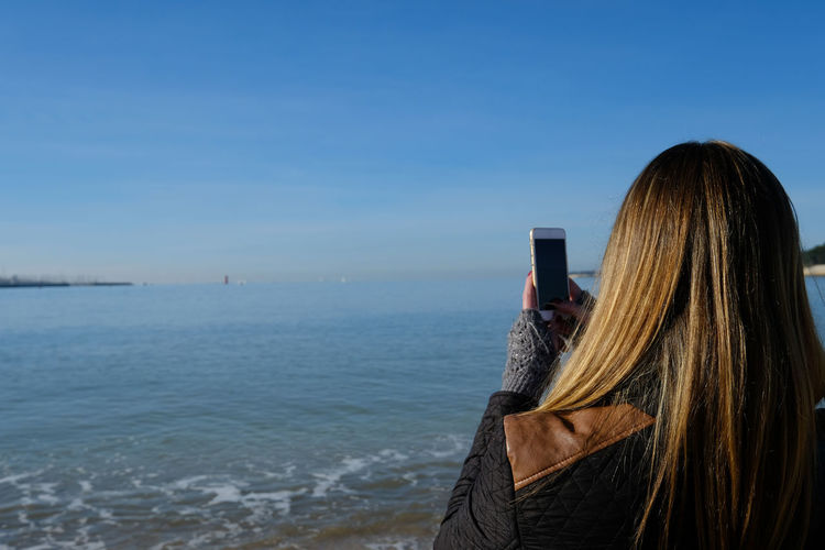 Rear view of woman photographing sea with smart phone against sky