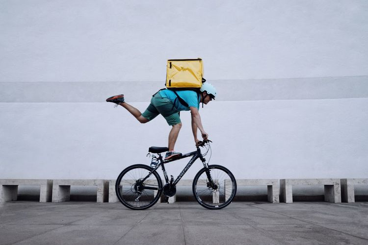 Man doing stunt on bicycle against wall
