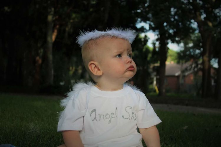 Baby In Angel Costume Sitting In Park