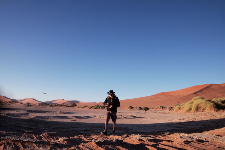 Full length of man on desert against clear sky