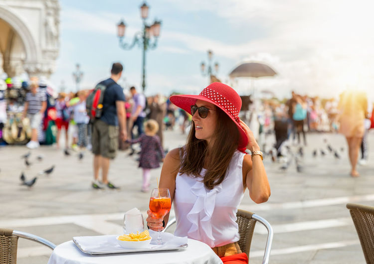 Elegant woman enjoys an aperitif on St. Mark's Square in Venice, Italy Aperitif Elegant Hat Woman Adult Alcohol Aperol City Day Drink Food And Drink Italy Leisure Activity Lifestyles Model Outdoors Real People Sidewalk Cafe Sitting Sky Summer Sun Table Vacations Venice