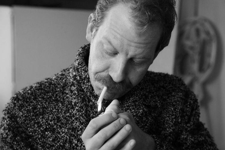 Close-Up Of Man Lighting Cigarette