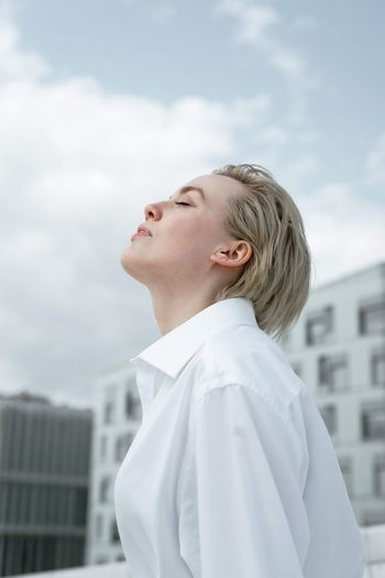 Side view of smiling young woman looking up in city against sky