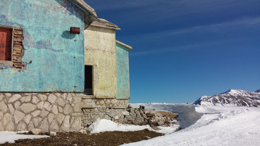 House by snowcapped field against blue sky