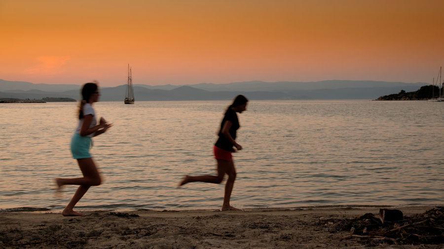 Woman enjoying on beach against sky during sunset