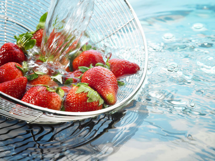 Close-up of strawberries being washed in colander