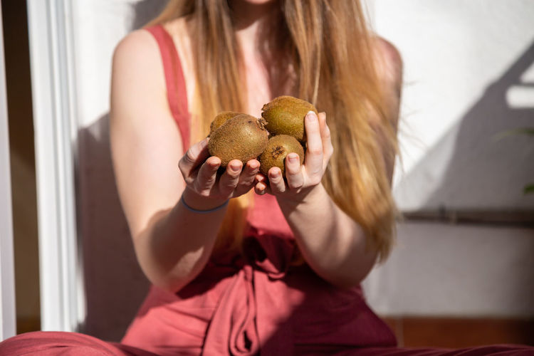 Young charming female in casual summer dress sitting on balcony and offering tropical fresh juicy kiwis Copy Space Portrait Girl Woman Kiwis Offering Recommend Balcony Terrace Summer Young Female Happy Joy Cheerful Beautiful Attractive Pretty Charming Sensual 💕 Cool Casual Dress Food Fruit Healthy Tropical Ripe Tasty Sweet Juicy Fresh Organic Natural Vitamins Sitting Holding Sunny Indoors  Crop